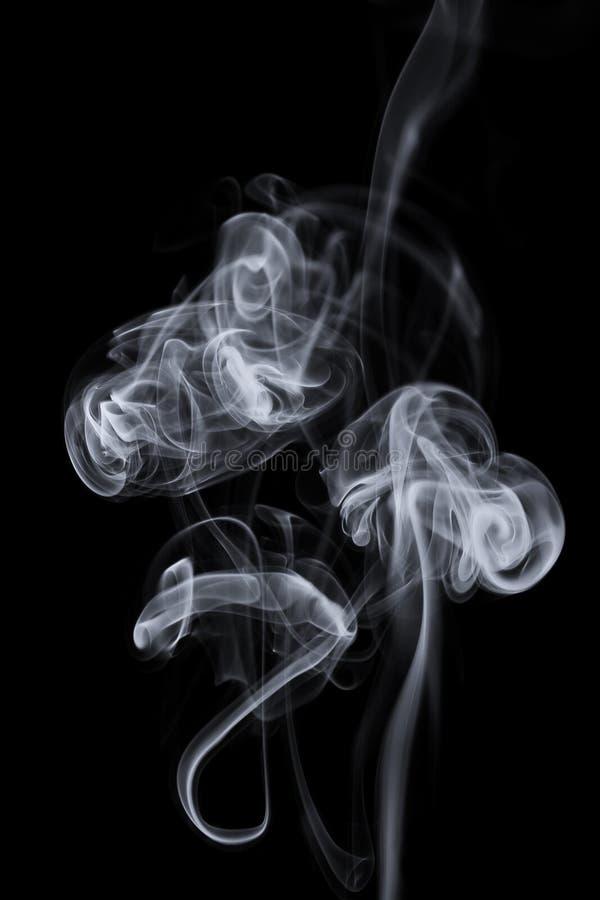 De rookwolken van de rook over zwarte achtergrond stock afbeelding