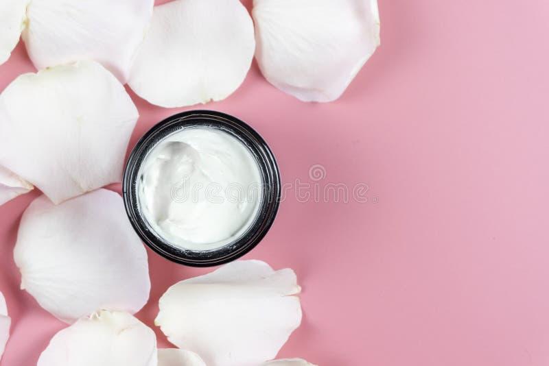 De room van de huidzorg en wit nam bloemblaadjes op roze achtergrond toe Hoogste mening royalty-vrije stock foto's