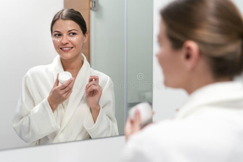 De room van de vrouwenholding in handen, die zich bij badkamers bevinden stock afbeeldingen