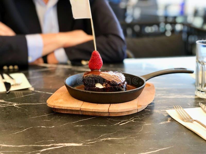 De room vulde de Hete die Brownie van de Chocoladecake met Aardbei in Pan bij Restaurant wordt gediend royalty-vrije stock foto