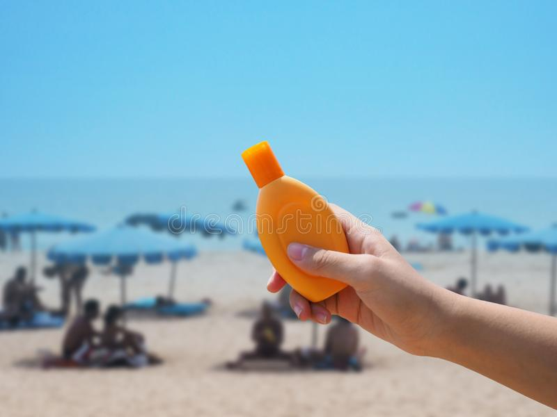 De roomfles van de handholding sunblock over de vage achtergrond van het de zomerstrand royalty-vrije stock fotografie