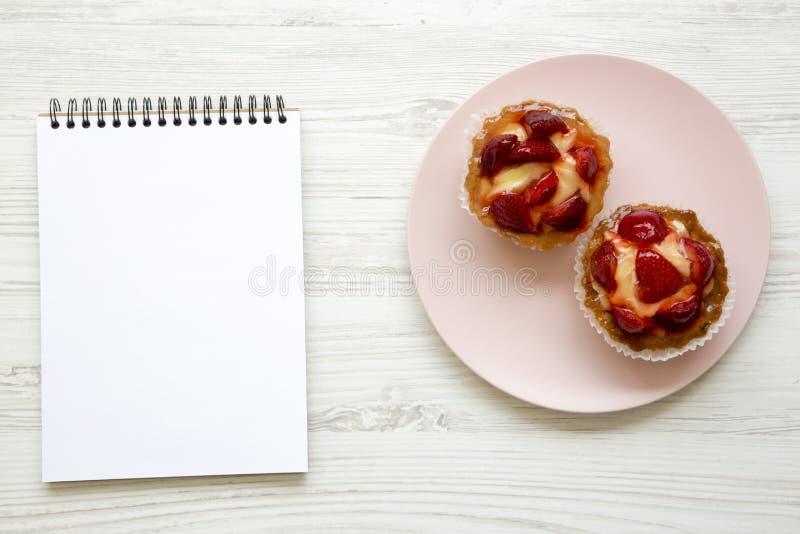 De roomkaastaartjes van de aardbeivanille op roze plaat met notitieboekje, hoogste mening stock foto's