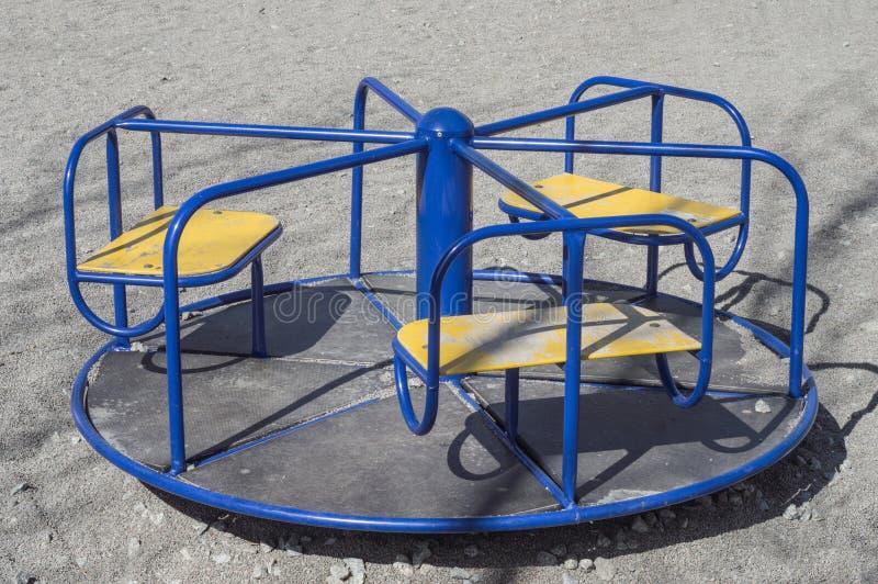De rotonde van kinderen (vrolijk-gaan-rond) op de speelplaats stock afbeelding