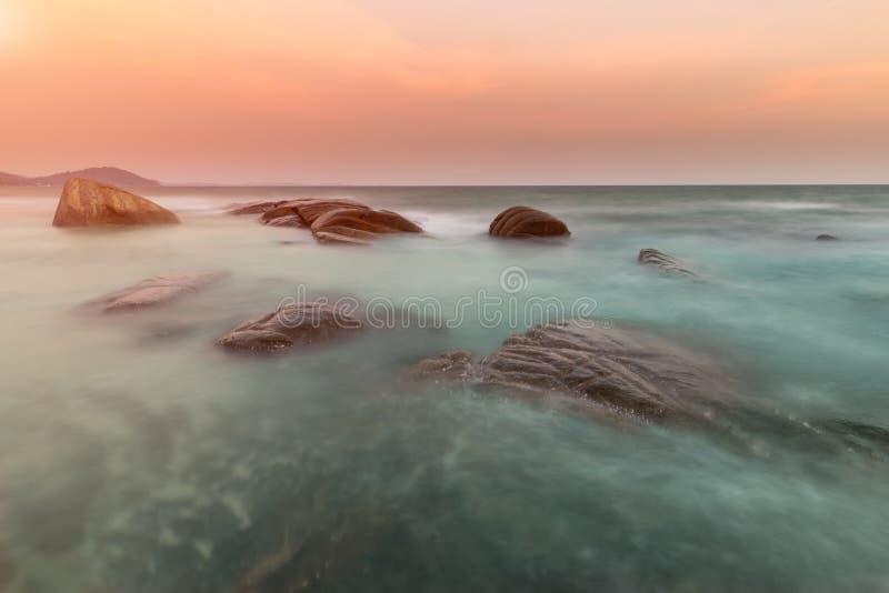 De rots en het overzees in de kleur van zonsondergang royalty-vrije stock afbeeldingen