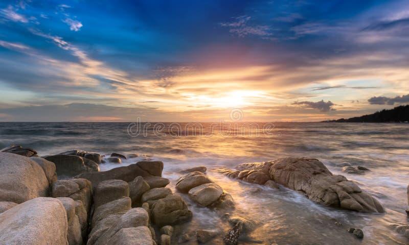 De rots en het overzees in de kleur van zonsondergangtijd royalty-vrije stock foto