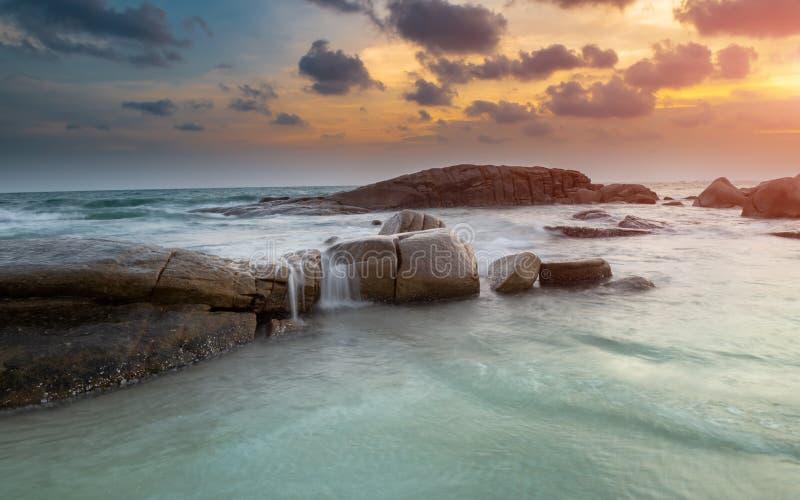 De rots en het overzees in de kleur van zonsondergangtijd stock afbeeldingen