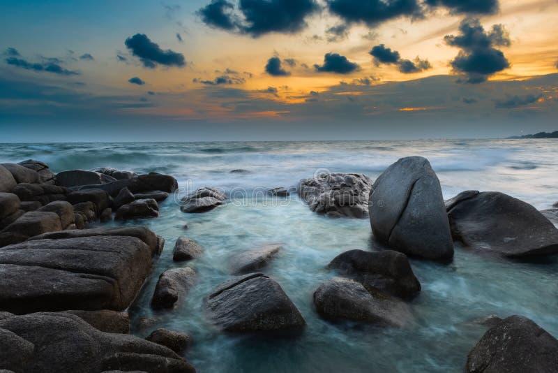 De rots en het overzees in de kleur van zonsondergangtijd stock foto's