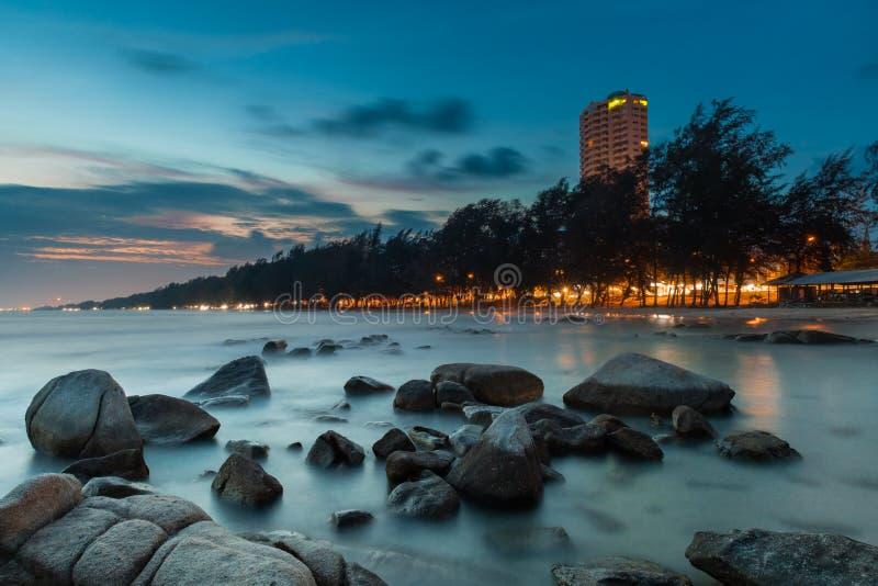 De rots en het overzees in de kleur van zonsondergangtijd royalty-vrije stock afbeelding