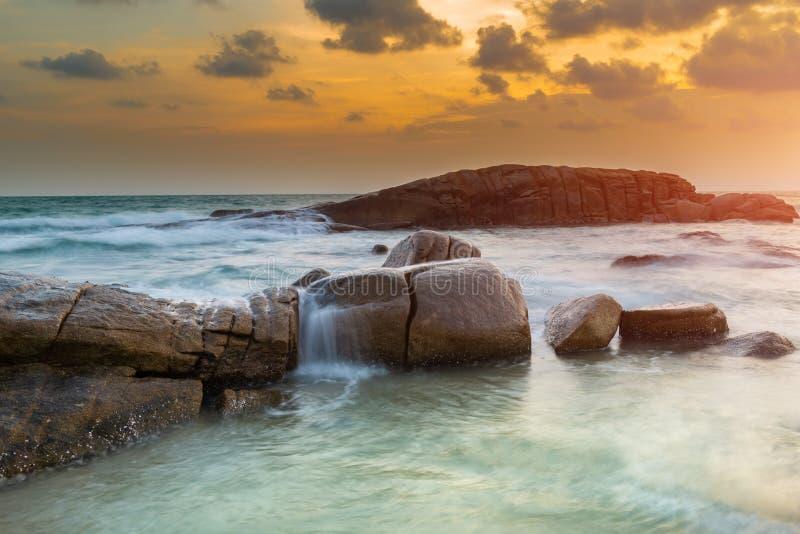 De rots en het overzees in de kleur van zonsondergangtijd royalty-vrije stock afbeeldingen