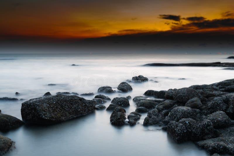 De rots en het overzees in de kleur van zonsondergangtijd stock foto