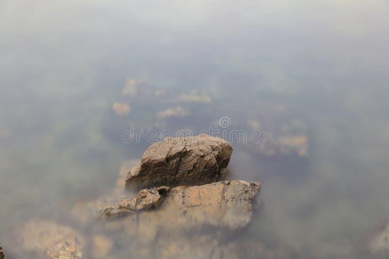 De rots van het de lijneffect van de golvenzweep op het strand stock afbeelding