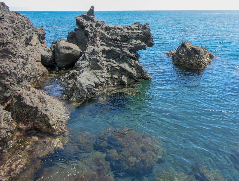 De rotsachtige klippen van abstracte vormen puilen boven de oppervlakte uit Glashelder overzees water Koraalondergrond onderwater royalty-vrije stock afbeelding