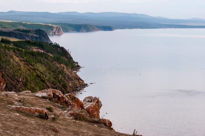De rotsachtige kust van Meer Baikal met vooruitstekende stenen en rood mos op hen stock afbeeldingen
