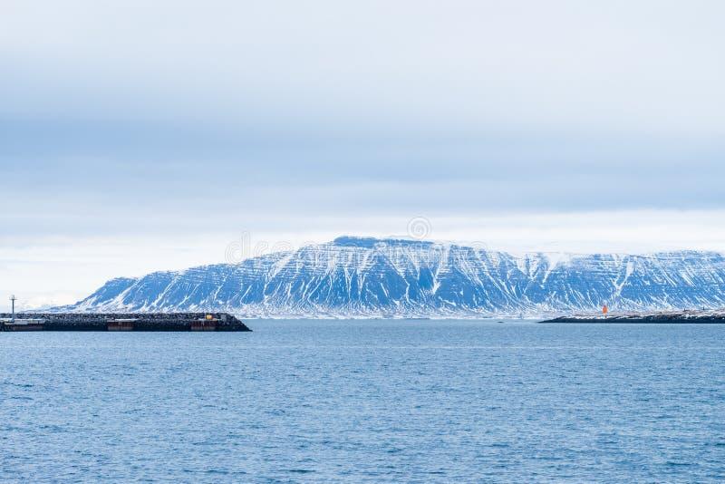 De rotsen of de Stenen remmen zeewater om kusterosie en snow-capped bergachtergrond te verhinderen royalty-vrije stock afbeeldingen