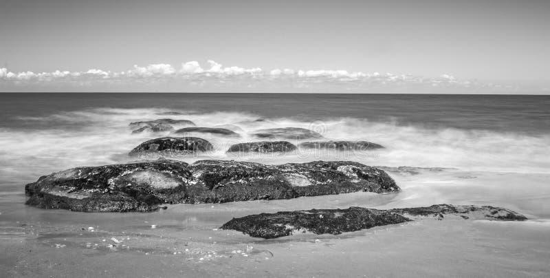 De rotsen op het strand snakken zwart-witte blootstelling stock foto's