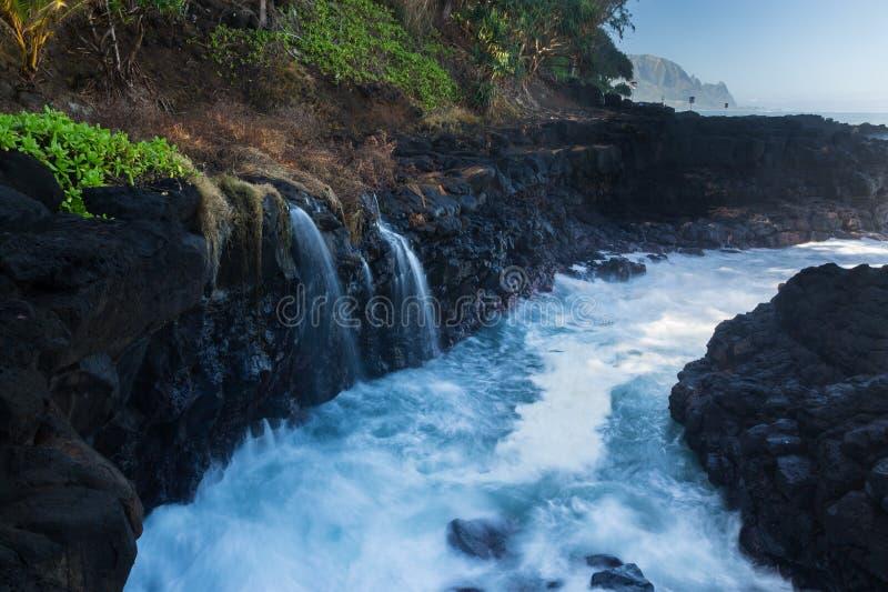 De rotsen van de golvenklap bij Queensbad Kauai stock afbeelding
