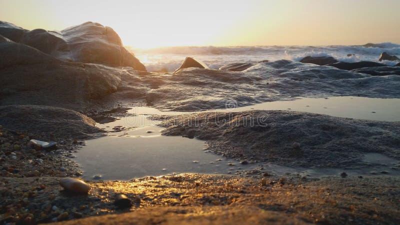 De rotsen van de zonsondergang op strand stock afbeelding