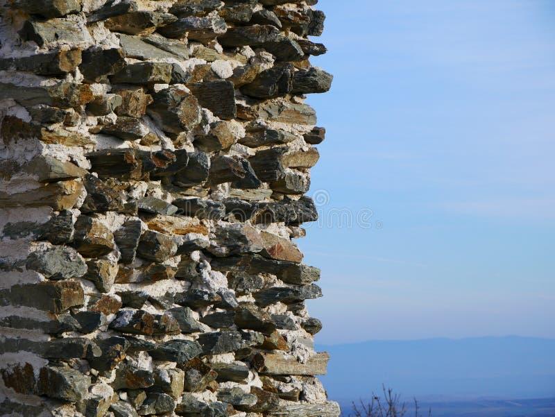 De rotspatroon van de steenmuur met bergen op achtergrond stock fotografie