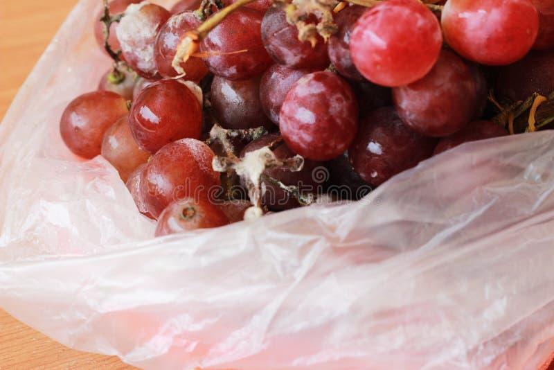 De rotte druiven zijn gevormd in een plastic zak op een bruine lijst royalty-vrije stock foto's