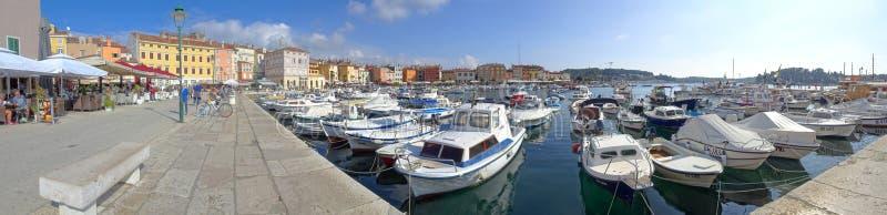 De Rovinj-promenade die van de waterkant de kleurrijke jachthaven en de boot-gevulde haven overzien stock foto's