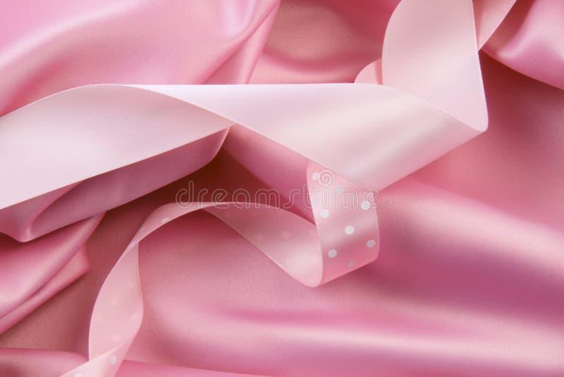 De roze achtergrond van de satijnzijde met linten stock foto