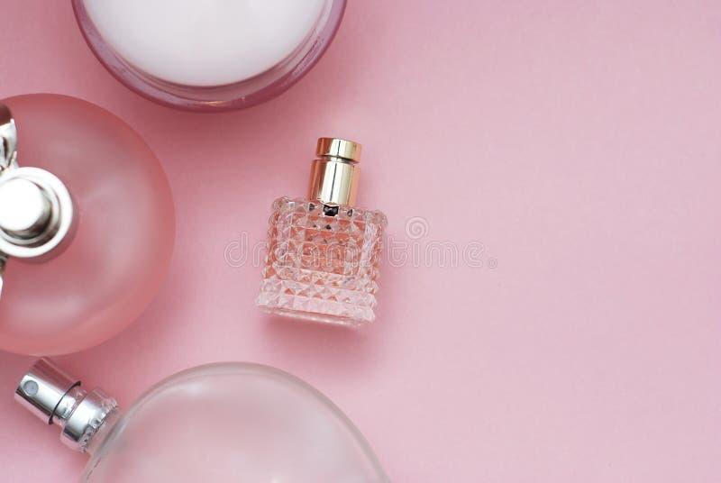 De roze achtergrond van parfumflessen Parfumerie, schoonheidsmiddelen, geurinzameling Vlak leg met exemplaarruimte Vrouwen en Moe stock foto
