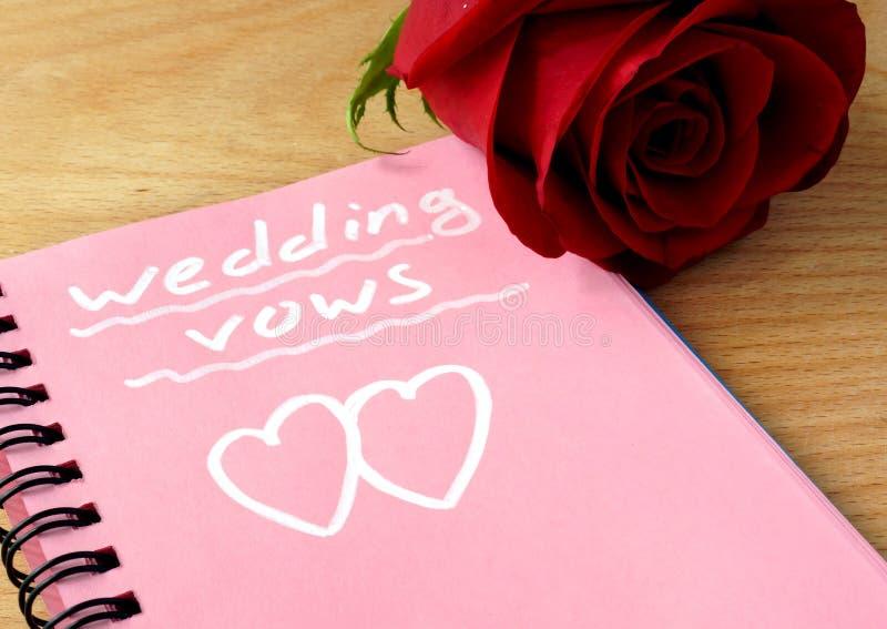 De roze blocnote met huwelijksgeloften en nam toe stock foto