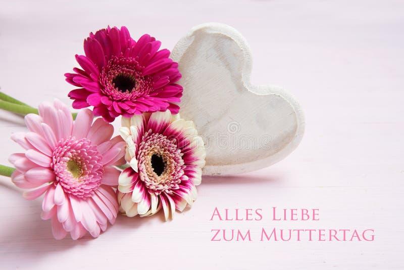 De roze bloemen en een wit geschilderd houten hart op een pastelkleur kleurden achtergrond, Duitse tekst Alles die Liebe zum Mutt stock afbeeldingen