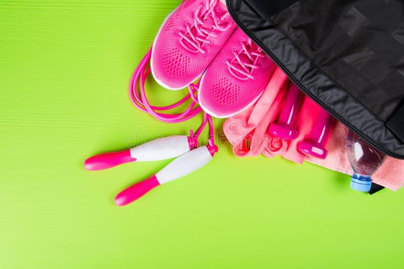 De roze kleren en de toebehoren voor fitness, een fles water, in sporten doen, op een lichtgroene achtergrond in zakken royalty-vrije stock foto's