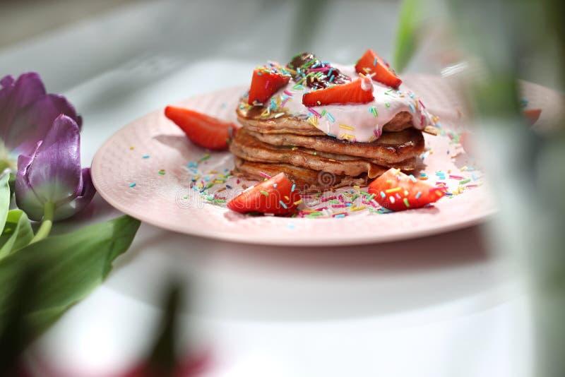 De roze pannekoeken met aardbeien, kwark en kleurrijke suiker bestrooit royalty-vrije stock foto's
