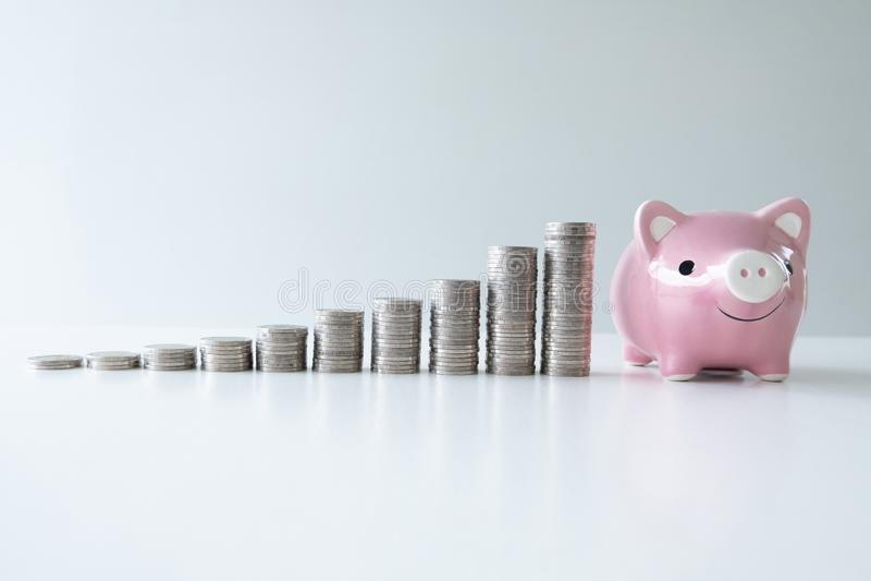 De roze piggy geldbank met muntstukkengrafiek, voert groeiende zaken aan succes en het sparen voor pensioneringsconcept op stock afbeelding