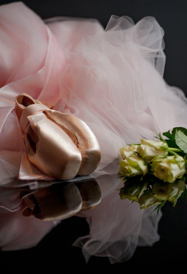 De roze schoenen van het satineballet pointe en witte rozen stock foto