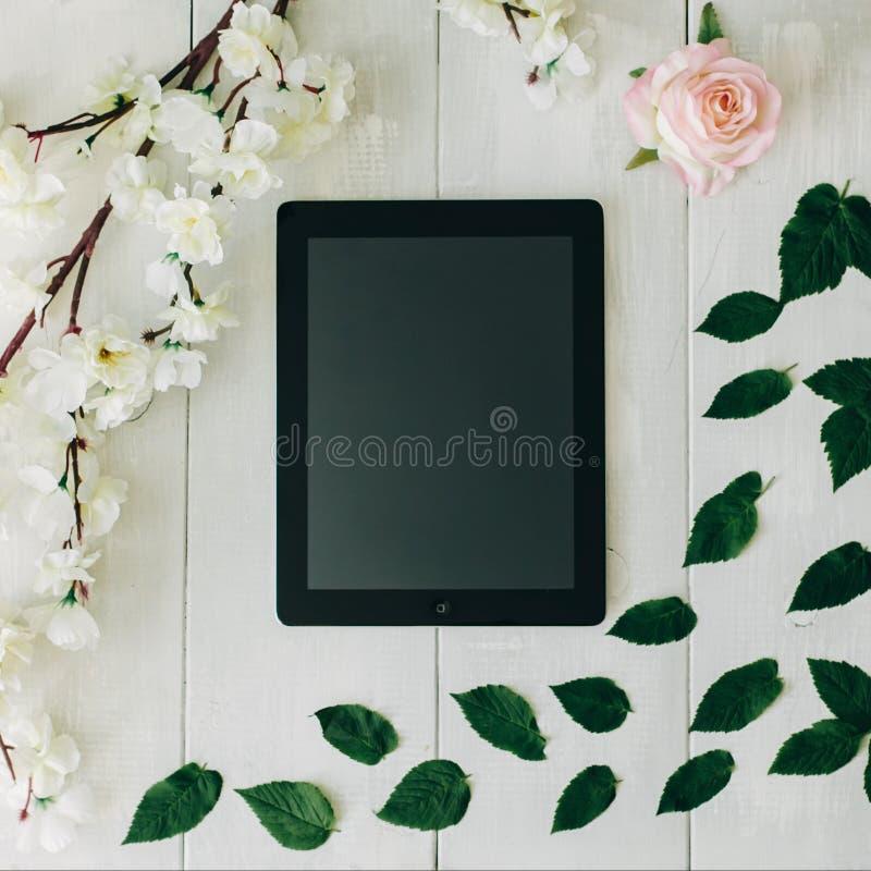 De roze tablet, nam bloem, groene bladeren en sakuratak op het witte houten bureau toe Uitstekende Kleuren royalty-vrije stock foto