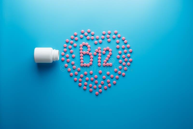 De roze tabletten in de vorm van B12 in het hart op een blauwe die achtergrond, van een wit wordt gemorst kunnen stock afbeeldingen