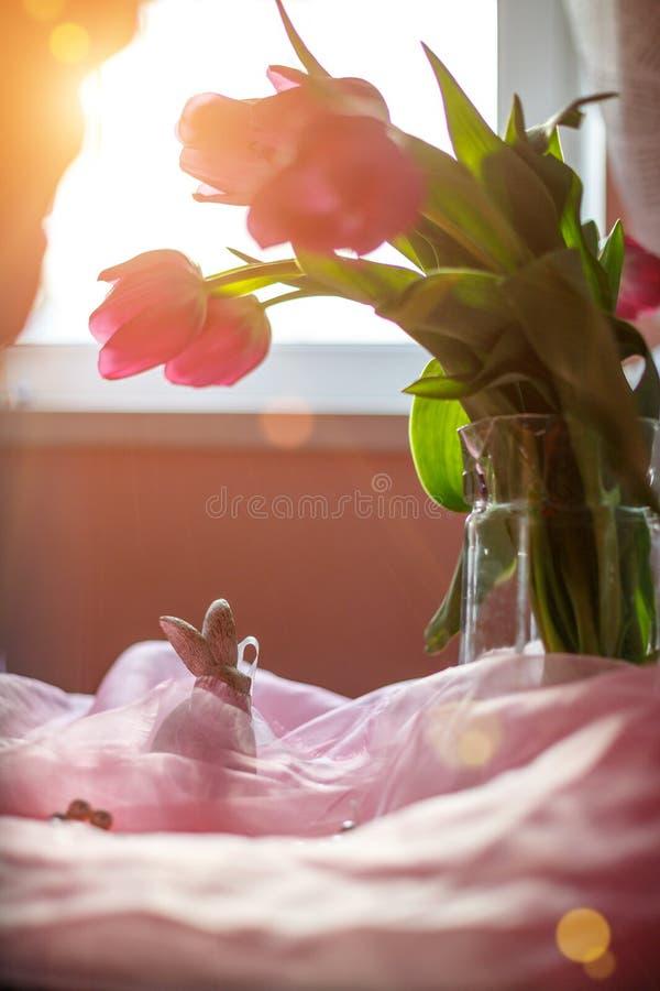 De roze tulpen in een vaas zijn op de muur dichtbij de venster zachte nadruk en het zonlicht royalty-vrije stock foto