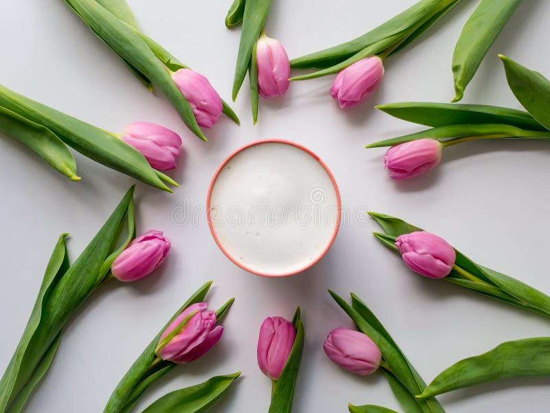 De roze tulpen schikten in een cirkel op een witte lijst met een cappuccinokop in het centrum Vlak leg royalty-vrije stock afbeeldingen