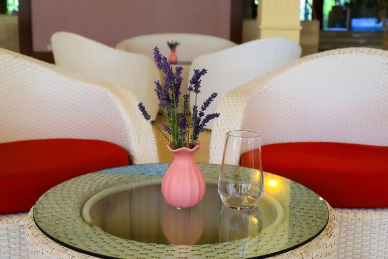 De roze vaas met een boeket van lavendel bloeit op een glaslijst met een transparant glas tegen de achtergrond van witte rode sto stock fotografie