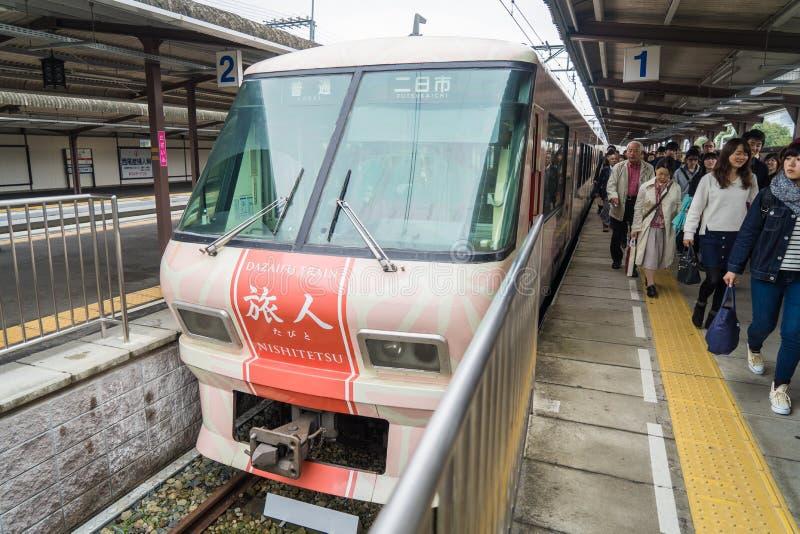 De roze verfraaide trein die looppas van Kegelpost aan Dazaifu-post royalty-vrije stock fotografie