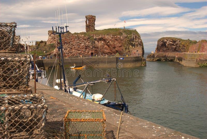 De ruïnes, de haven en de vissersboten en de netten van het Dunbarkasteel stock afbeelding