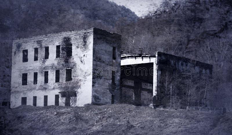 De ruïnes van berghuis met drie verdiepingen met hangaar royalty-vrije stock afbeeldingen