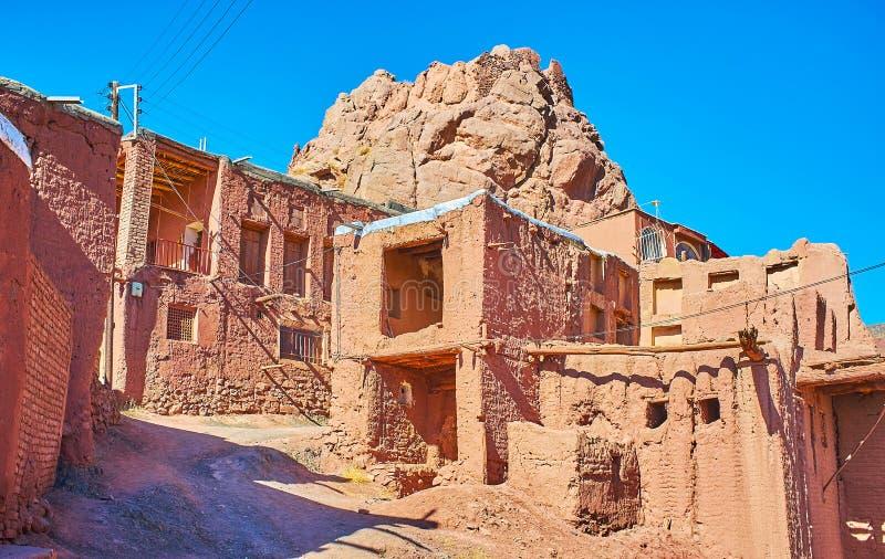 De ruïnes van oud fort achter de middeleeuwse adobehuizen in heuvelige straat van Abyaneh-dorp stock afbeeldingen