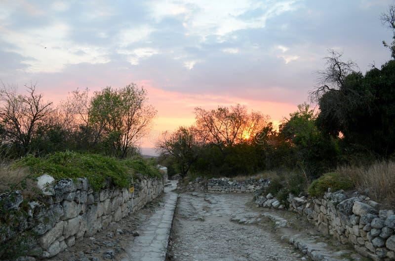 De ruïnes van de oude bedekte weg op de achtergrond van de hemel van de de zomerzonsondergang in roze, purpere en blauwe kleuren stock foto