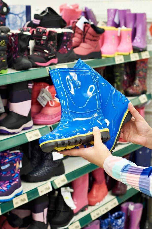 De rubberlaarzen van kinderen in handen van koper bij opslag stock afbeelding