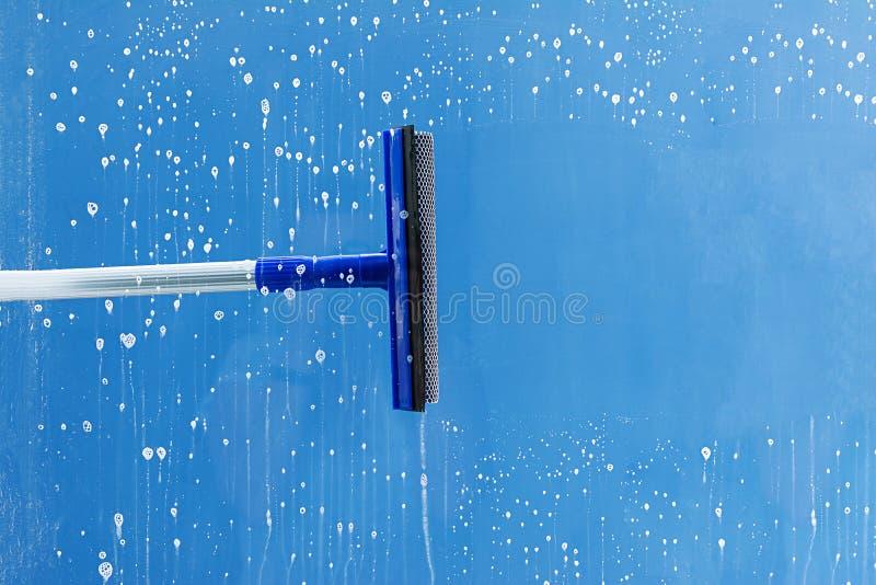 De rubberrubberschuiver maakt venster schoon Ontruimt een streep van ingezeept venster Het schoonmaken de dienstconcept stock foto