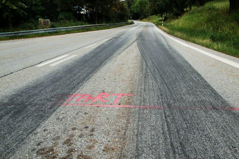 De rubbersporen van de raceauto's stock foto's