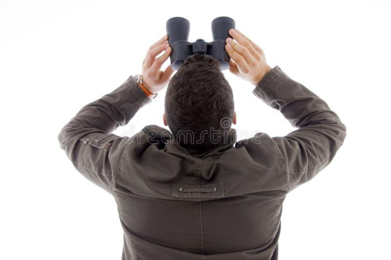 De rug stelt van de mens gebruikend een paar verrekijkers stock afbeelding