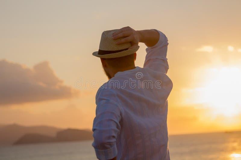 De rug van een mens in een hoed tegen de achtergrond van het overzees in de heldere gouden stralen van de zon bij zonsopgang stock foto
