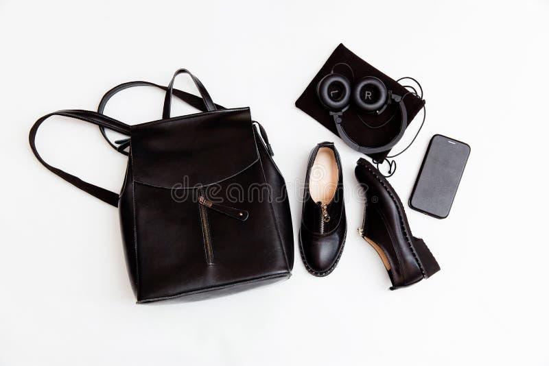 De rugzak, de schoenen, de telefoon en de hoofdtelefoons van vrouwen in zwarte De toebehoren van de het leermanier van vrouwen Vl stock afbeelding