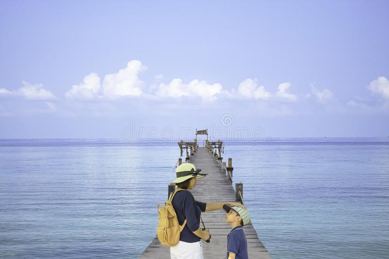 De rugzak van de moederschouder en zoon op de houten boot van de brugpijler in het overzees en de heldere hemel die in Koh Kood,  stock afbeeldingen