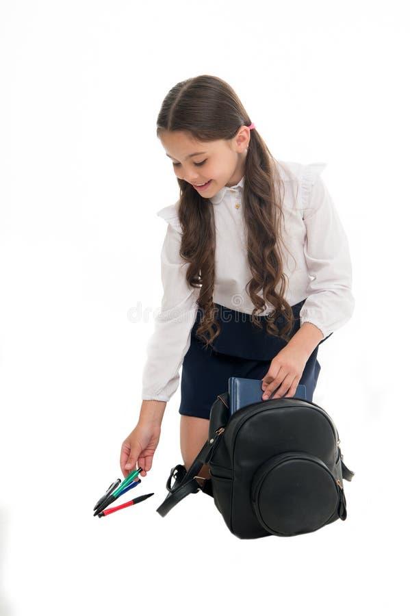De rugzak van de schoolmeisjeverpakking op wit wordt geïsoleerd dat Weinig kind zette pen en boek in zak Pakrugzak voor lessen stock foto's